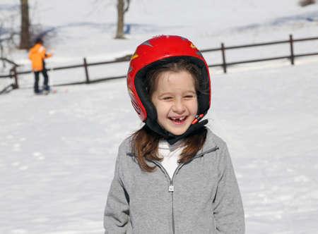 casco rojo: ni�a sonriente con el casco rojo en la nieve en invierno Foto de archivo