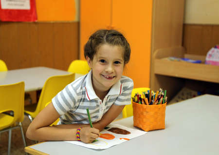 pretty little girl: pretty little girl while drawing with the pencil colours at school Stock Photo