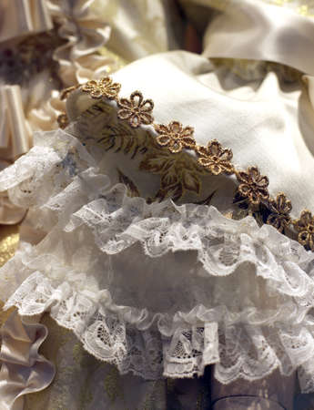 detail of an old wedding dress in ivory color with floral decorations with gold wire
