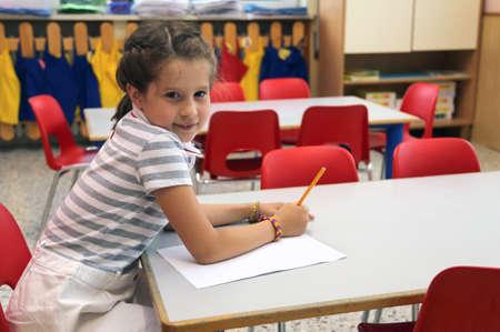 pretty little girl: pretty little girl in class writes at school