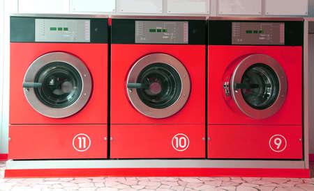 washing machines: three large washing machines in laundromats