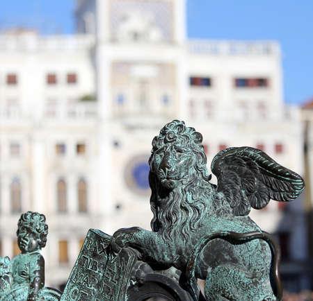 leon con alas: símbolo del león alado de la Serenísima República de Venecia y la torre del reloj en el fondo Foto de archivo