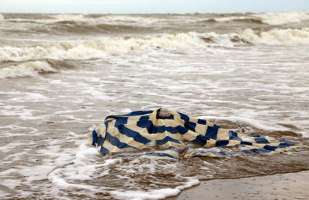 forecasts: Broken beach umbrella in the sea after the terrible storm Stock Photo