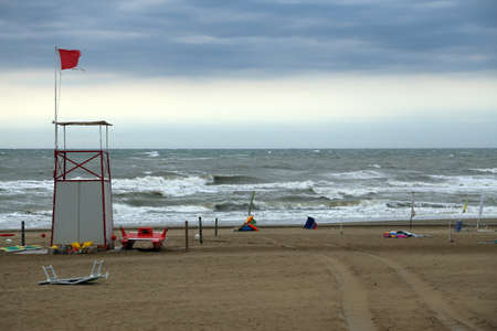 forecasts: Lifeguard Tower on the beach with the sea very rough and agitated after the storm