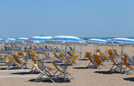 sultry: sunbeds with umbrellas in sunny beach in summer