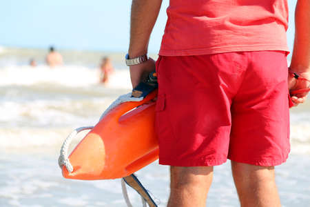 drowning: muscled lifeguard with the rescue can to rescue the swimmers in case of drowning