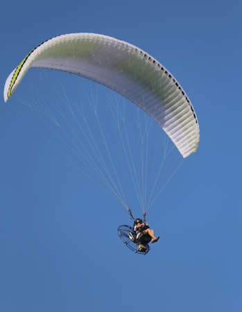 daredevil: Daredevil pilot with the motor glider flies fast in sky blue