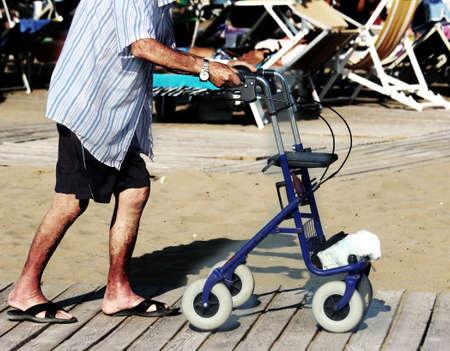 lame: elderly man walking with Walker on the beach in summer