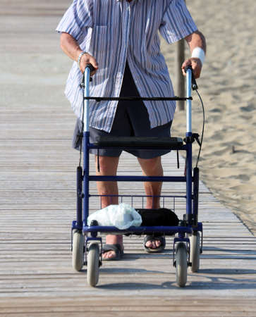 ambulatory: old man walking with Walker on the beach in summer Stock Photo