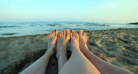 nudist: four barefoot by a couple by the sea in summer