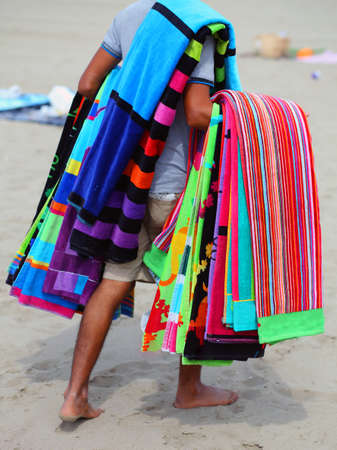 clandestine: African peddler of towels and beach towels on the beach