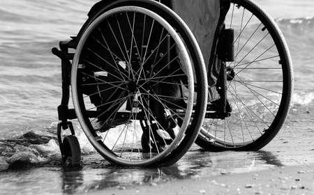 Black wheelchair beside the sea on sandy beach Stock Photo