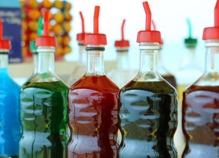 creams: bottles of colored syrup for preparing ice creams in summer on the beach