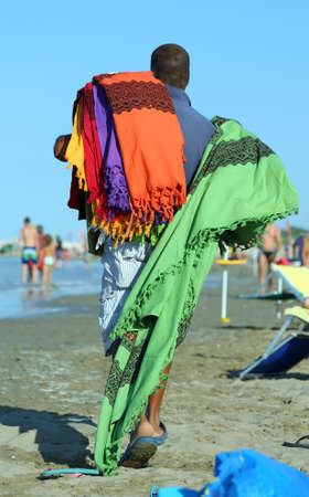 clandestine: street vendor of fabrics and Slipcovers on the beach in summer