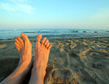 nudist: two bare feet of a man by the sea in summer