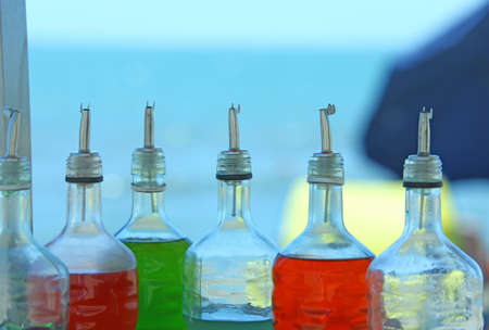 creams: many bottles of syrup for preparing ice creams in summer on the beach Stock Photo