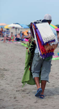 clandestine: African peddler of towels and beach towels on the beach in summer