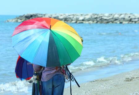 clandestine: Elder peddler of colorful umbrellas on the beach in summer