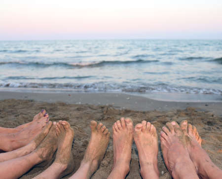 big toe: ten feet of a family by the sea on the beach in summer Stock Photo