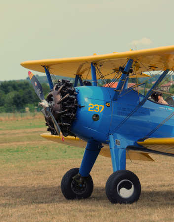 aviators: Thiene, Vicenza - Italy. 26th July, 2015: important air show called FlighThiene in Thiene Airport near Vicenza City in Northen Italy with many historical and modern airplanes. Blue biplane with large propeller