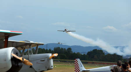 aviators: Thiene, Vicenza - Italy. 26th July, 2015: important air show called FlighThiene in Thiene Airport near Vicenza City in Northen Italy with many historical and modern airplanes. Fantastic acrobatic exhibition of antique aircraft with engine smoke over the a