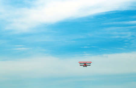 a war historian: Ancient red triplane flies in the blue sky Stock Photo