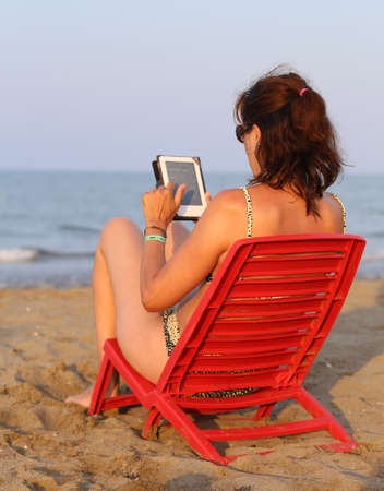 fiestas electronicas: tanned woman reads the ebook on the seashore in the summer while his children playing on the beach