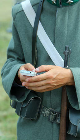 anachronistic: Rifle and Smartphone of a soldier during reenactment of war