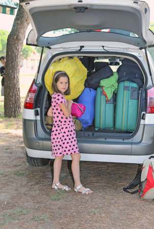 duffle: pretty little girl with hearts dress loads the baggage car in summer and her brother near the tree