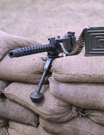 a war historian: historic machine gun with bullets over the sandbags in trench warfare  used in World War II by the allies