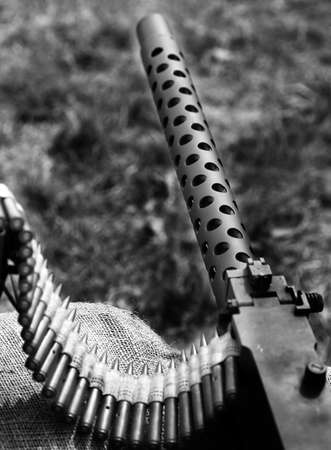 historian: historic machine gun with bullets over the sandbags used in trench warfare in World War II by the allies