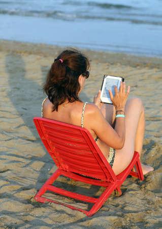 fiestas electronicas: mujer lee el libro electr�nico en la playa en verano Foto de archivo