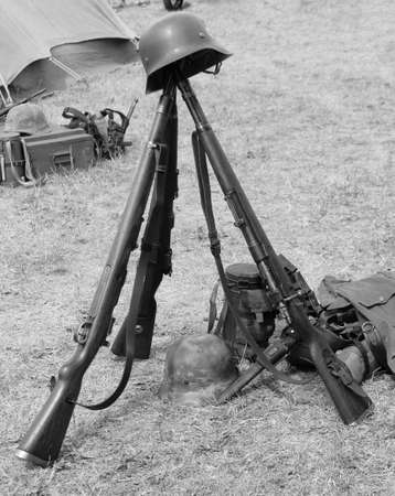 rifleman: three old war rifles and helmets of dead soldier at war Stock Photo