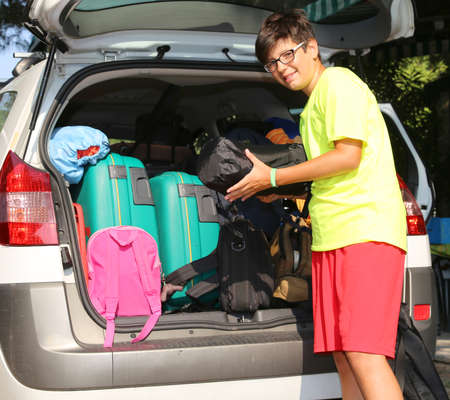 duffle: smiling boy loads bags in the baggage car in summer