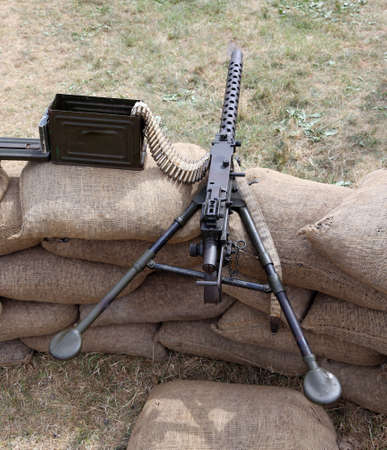 a war historian: machine gun with ammunitions over the sandbags in the trench war