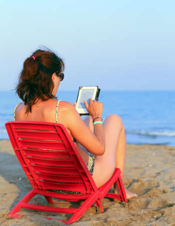 Pretty woman on red chair reads the ebook on the beach by the woman reads the ebook on the beach by the sea photo fandeluxe Ebook collections