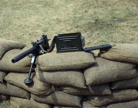 a war historian: machine gun with bullets over the sandbags in the trench war Stock Photo