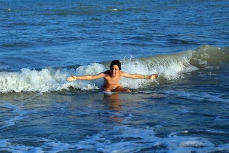 encrespado: ni�o que juega en el mar saltando las olas del mar picado en verano durante las vacaciones de verano en el Mediterr�neo