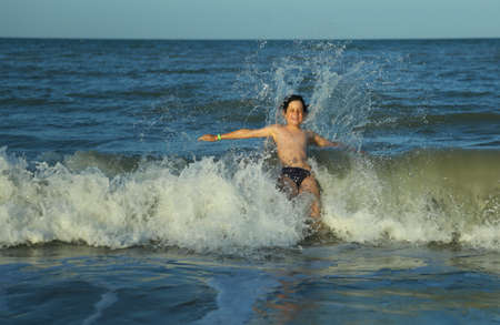 courageous young child plunges over the waves of the choppy sea
