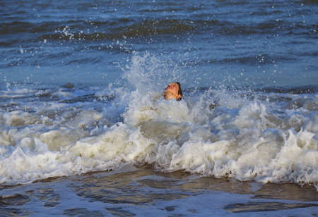 intrepid and courageous young child plunges over the waves of the choppy sea Stock Photo
