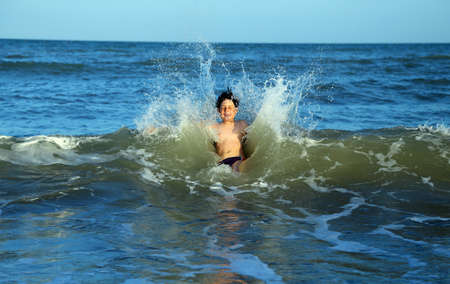 intrepid: intrepid young child plunges over the waves of the choppy sea in summer Stock Photo