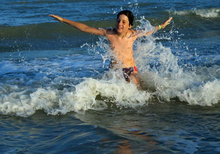 choppy: young boy splash in the waves of the choppy sea in summer Stock Photo