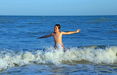 choppy: child playing in sea jumping the waves of choppy sea in summer during the summer holidays in the Mediterranean