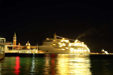 ve: Venice, VE - Italy. 10th July, 2015: huge cruise ship departs from Venice at night with all the lights on for a cruise on the Mediterranean Sea with many tourists on board