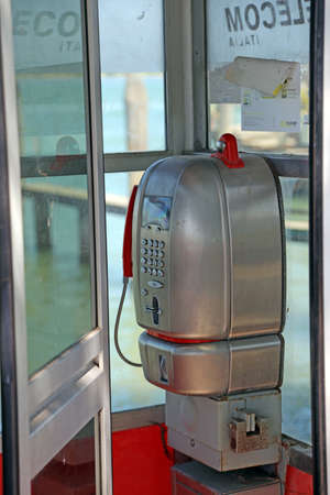 italia: Treporti, Venice, VE - Italy. 14th July, 2015: old Italian phone booth of Telecom Italia Company working with token or magnetic card, now out of order near the harbor Editorial