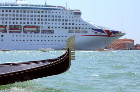 ship bow: Venice, VE - Italy. 14th July, 2015: huge cruise ship and small bow of the gondola in the Canale della Giudecca near Saint Mark Square