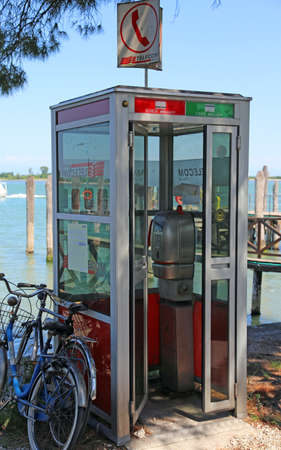 Treporti, Venice, VE - Italy. 14th July, 2015: old Italian phone booth of Telecom Italia Company working with token or magnetic card, now out of order near the harbor Editorial