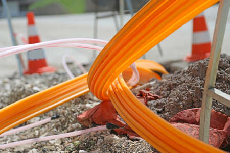Orange pipes for fiber optics in a large city road construction to connect high speed internet Stock Photo - 43389957