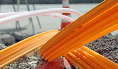 Orange pipes for fiber optics in a large city road construction to connect high speed internet