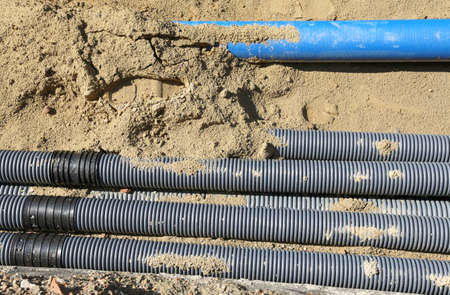 an excavation: many corrugated pipes for laying electric cables in the excavation in road construction